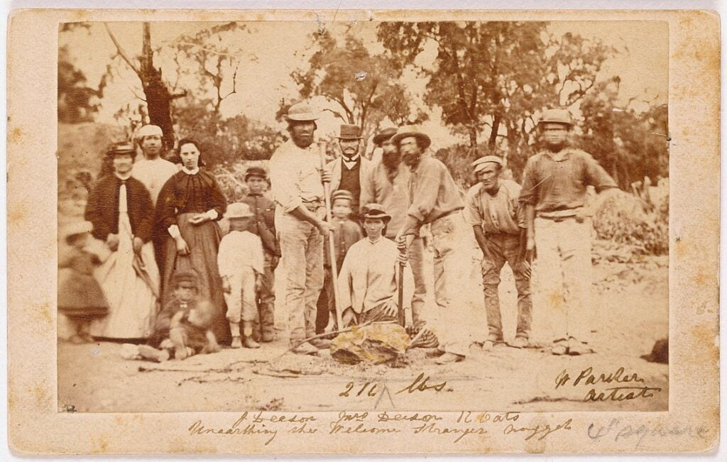 Miners and their wives posing with the finders of the nugget, Richard Oates, John Deason and his wife. The Welcome Stranger Nugget was discovered on 5 February 1869