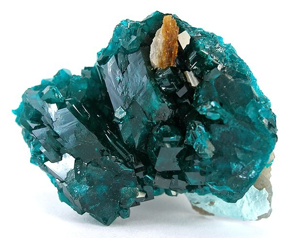 Dioptase, Baryte, Plancheite Locality: Kaokoveld Plateau, Kunene Region, Namibia Size: 3.8 x 3.1 x 1.4 cm. A little orange barite perched atop! The central dioptase is 1.3 cm and pristine. The one on the edge is larger, but incomplete at its edge.